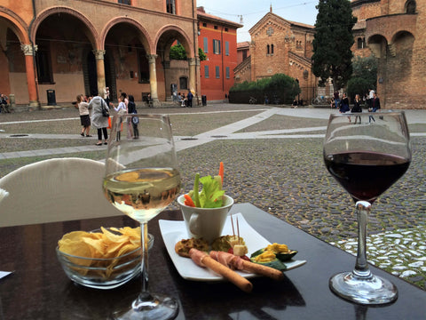 wine and appetizers in a small plaza in bologna, italy