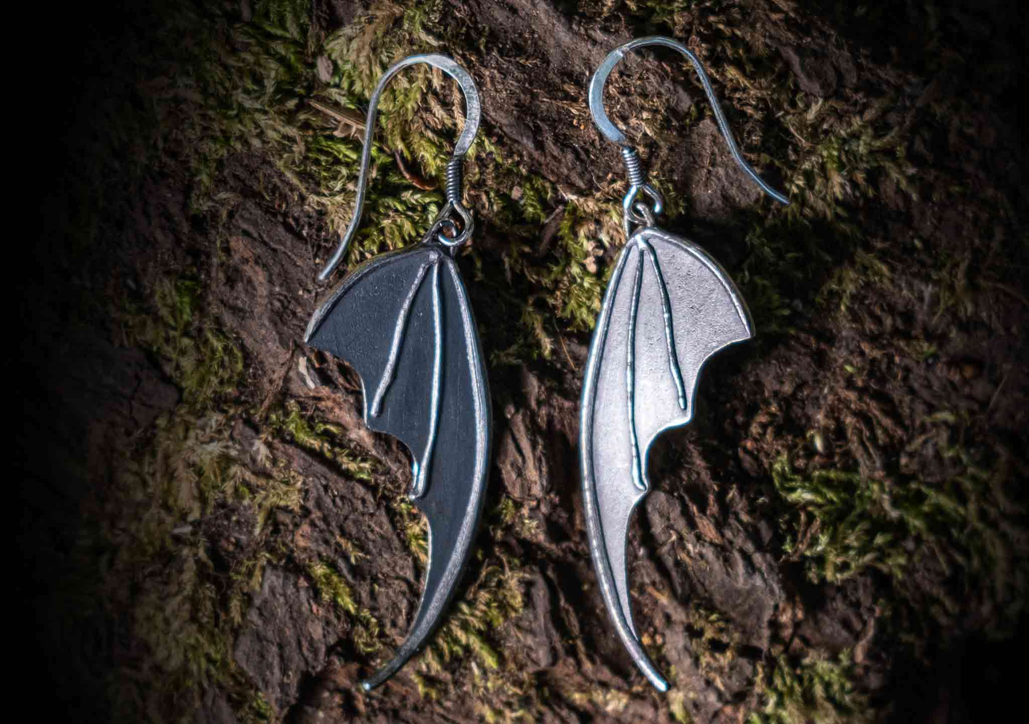 bat wing silver earrings on a moss covered tree bark