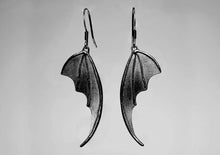 bat wing silver earrings on a light background