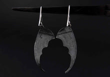 bat wing silver earrings on a black background