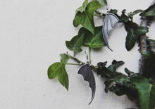 bat wing silver earrings hanging on ivy