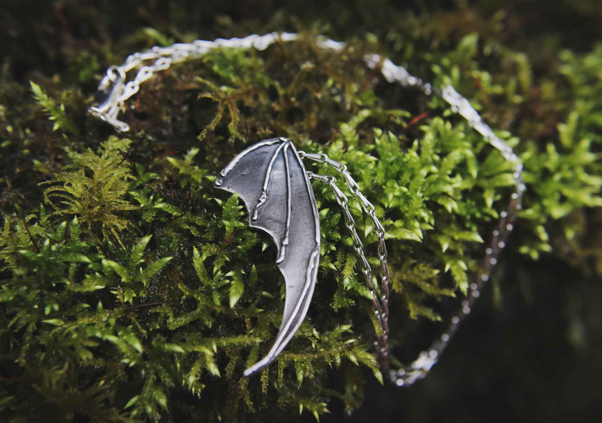 bat wing silver pendant on a moss background