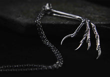 silver blackbird claw on a dark metal surface