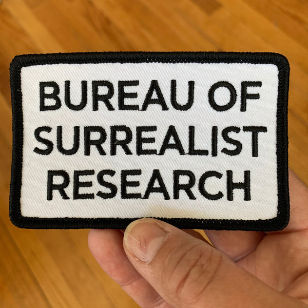 Iron-on patch with text: BUREAU OF SURREALIST RESEARCH in black lettering on white background with a black border