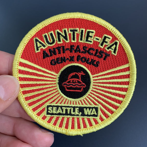 aunti-fa patch. 3 inches round, red stitched background with yellow border, saying ANTI-FASCIST GEN-X FOLKS, seattle WA, with image of a pie with a bomb in it, rays radiating out.