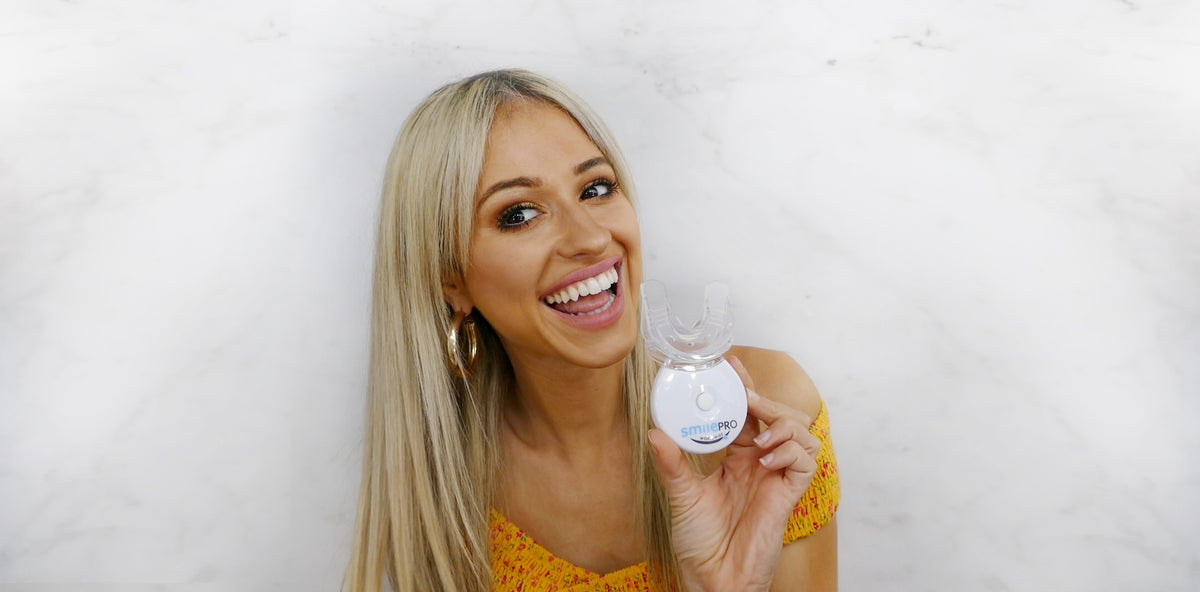 Woman holding teeth whitening device