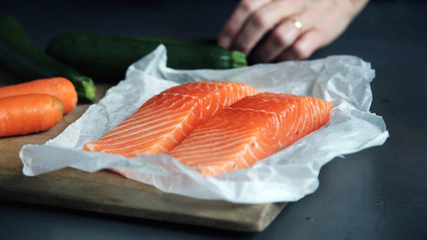 Foods to Get Rid of Acne - two slices of raw salmon sitting on an open paper on a table