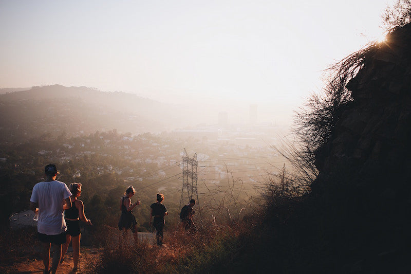 Causes of Acne on Cheeks - pollution. Group of hikers walking in hills of Los Angeles, smog in background.