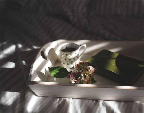 Foods to Get Rid of Acne - cup of green tea sitting on a white breakfast tray with a flower and a book