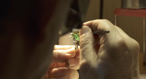 artisan painting a cufflink by hand with enamel