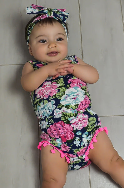 Floral toddler romper with pink pom poms.
