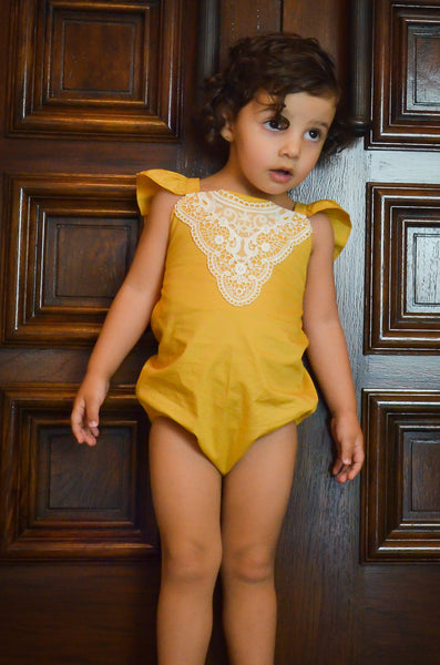 Vintage mustard romper with adjustable tie up frill straps for your toddler. Beautiful white lace detail and frilly tie back.
