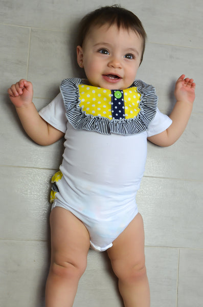 white romper with striped and polka dot ruffles on the collar and the bum.