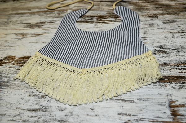 A unique grey striped vintage style bib with tassels for your baby.