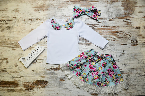 White long sleeve top with floral collar, and floral skirt with lace detail. Bonus matching floral hair accessory.