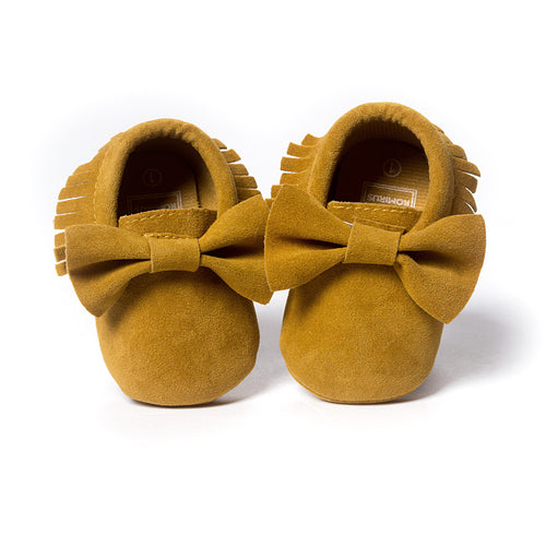Soft sole moccasin baby shoes deep mustard colour with bow and tassel trim.