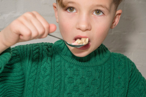 Boy eating cereal in a green knitted jumper
