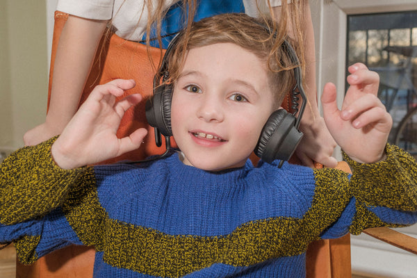 Child listening to music on headphones in a knitted jumper