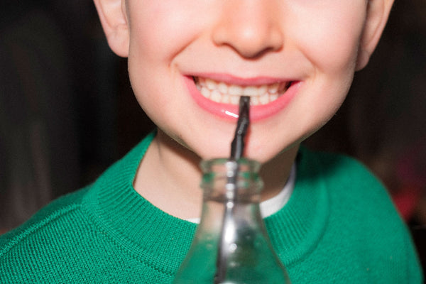 Close up of a boys mouth with a glass bottle and straw