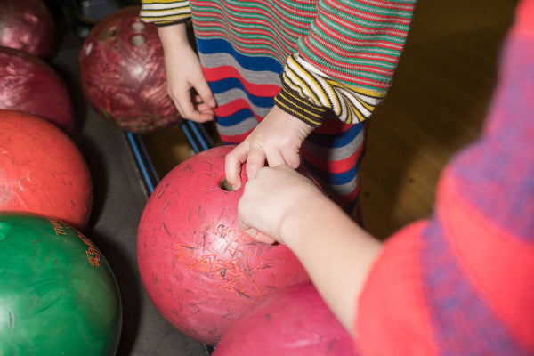 Children's hands selecting a bowling ball