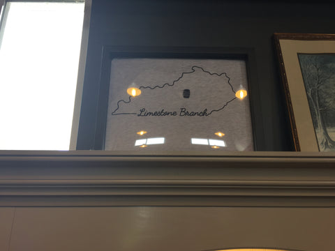 Retail Display of tee shirts framed and displayed in a Shart T Shirt Frame Display Case at Limestone Branch Distillery
