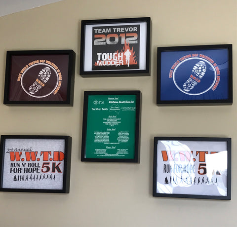 Office Display of tee shirts framed and displayed in a Shart T Shirt Frame Display Case