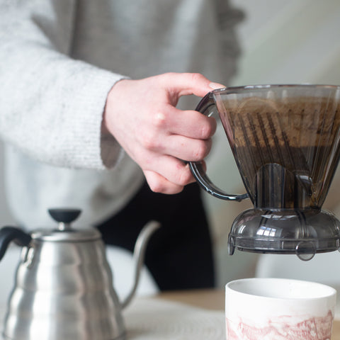 Person lifting a Clever Dripper coffee maker onto a cup