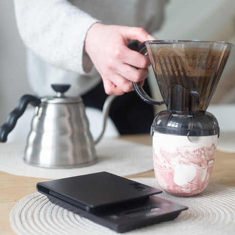 Person putting Clever Dripper onto cup which stands on a table
