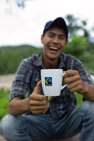 Fairtrade logo on coffee cup with Fairtrade farmer holding and smiling