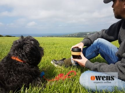 Man holding coffee in a KeepCup reusable cup next to black dog sitting in grass