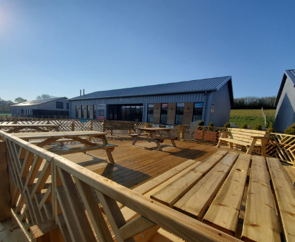 Decking area with tables and benches outside The Roastery at Owens Coffee