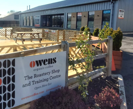 Owens Coffee sign in front of decking area with The Roastery building in background
