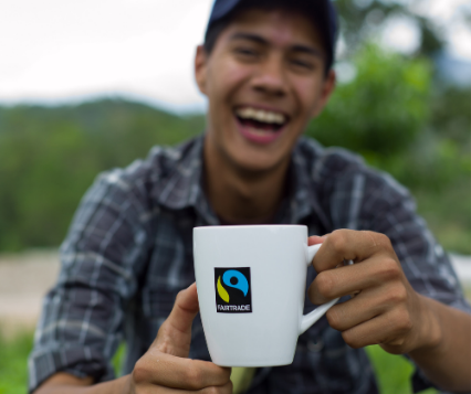 Man smiling and drinking from Fairtrade coffee mug