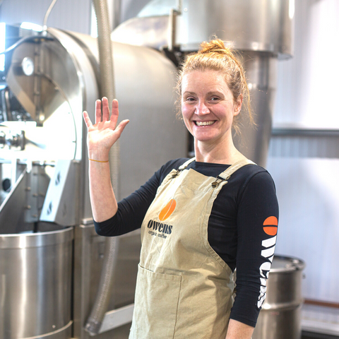 Woman in Owens Coffee apron smiling and waving with coffee roaster behind her