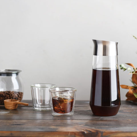 Kinto Luce Cold Brew carafe with cold brew in it on a table with coffee cups