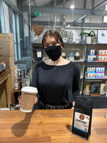 Woman serving Owens Coffee takeaway and organic coffee beans at trade counter