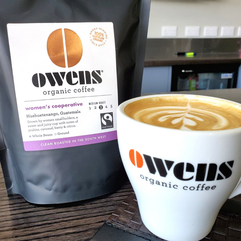 Bag of Owens Coffee Womens Cooperative Single Origin Coffee next to a mug with Owens Organic Coffee written on it and latte art in it