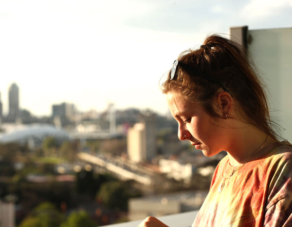 Picture of a young woman, evening sun in her face, with city view in the background