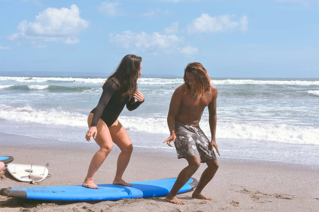 surf guide teaching a girl how to surf on the beach