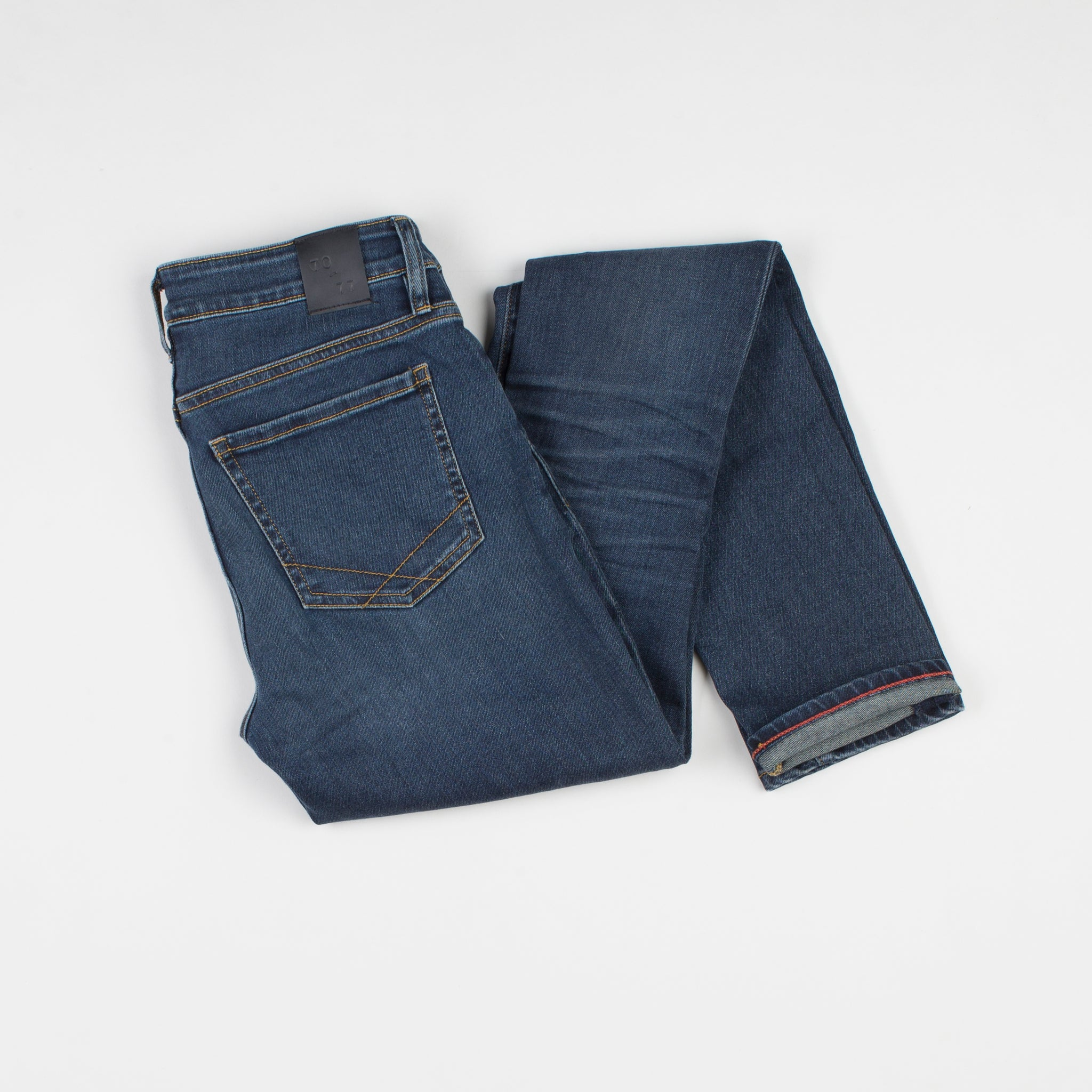 angle: saucepan  Raleigh Denim Workshop Surry mid-rise thin jeans in a dark wash, back view
