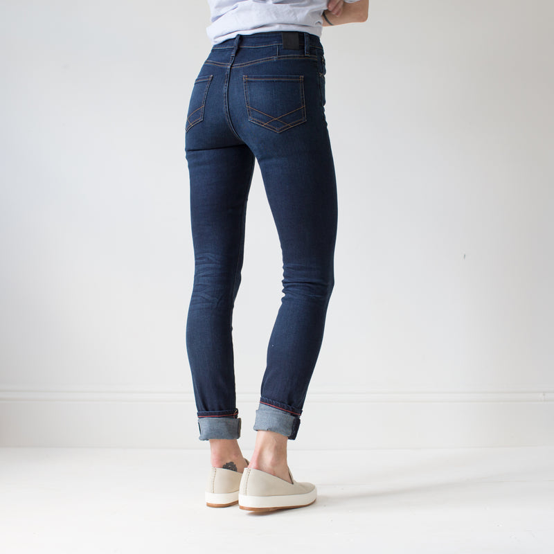 angle: phantom  A model wears Raleigh Denim Workshop Haywood high-rise skinny fit dark blue jeans, back view