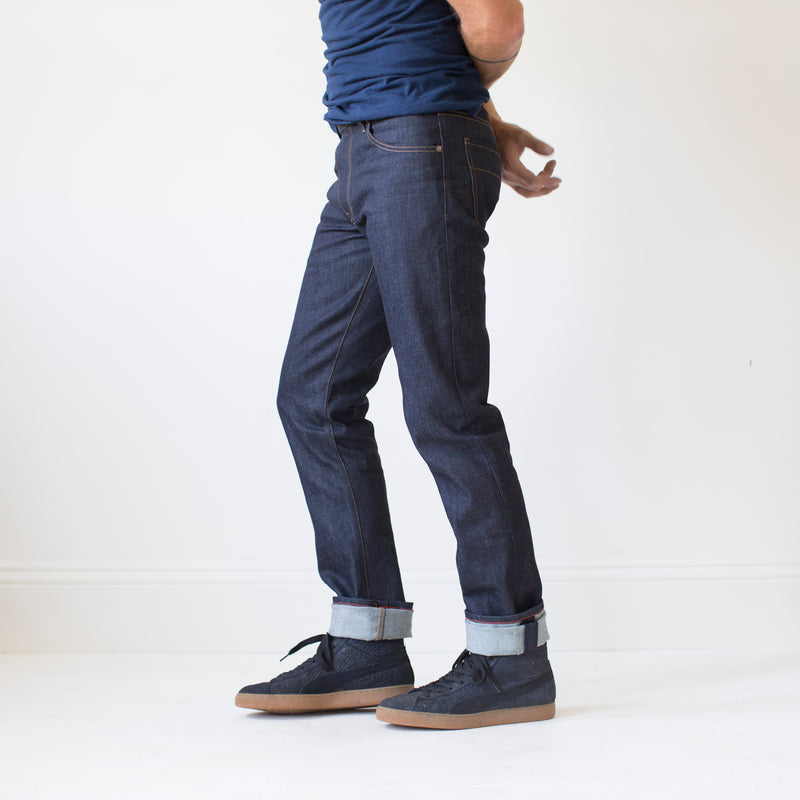 angle: 319 raw  A model wears Raleigh Denim Workshop Jones thin fit raw jeans in blue, side view
