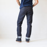 angle: 319 raw  A model wears Raleigh Denim Workshop Jones thin fit raw jeans in blue, back view