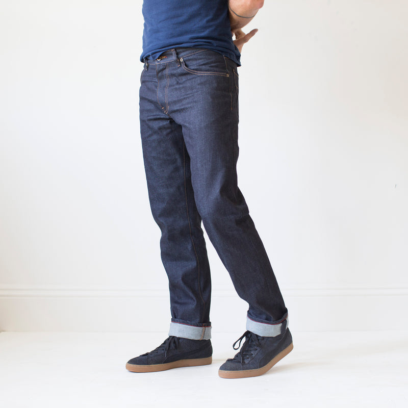angle: 319 raw  A model wears Raleigh Denim Workshop Alexander work fit jeans raw in blue, front view