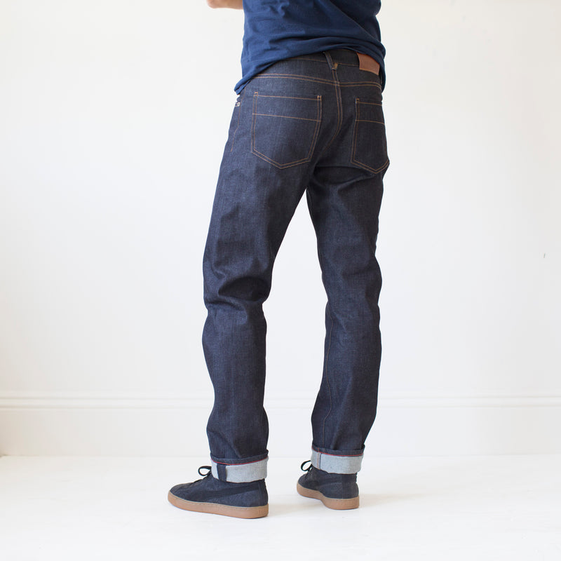 angle: 319 raw  A model wears Raleigh Denim Workshop Alexander work fit jeans raw in blue, back view