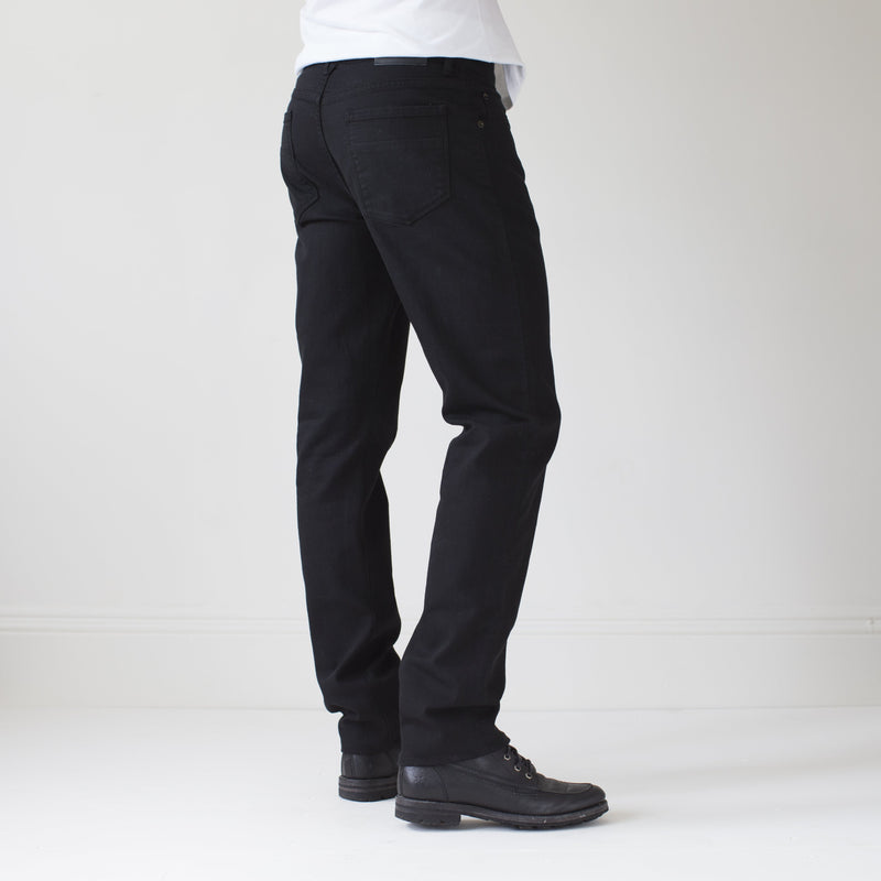 angle: black  A model wears Raleigh Denim Workshop Alexander work fit stretch pants in black, side