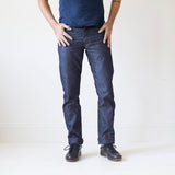 angle hover: wolf grey  A model wears Raleigh Denim Workshop men's Jones thin fit selvage raw denim jeans in grey, front view