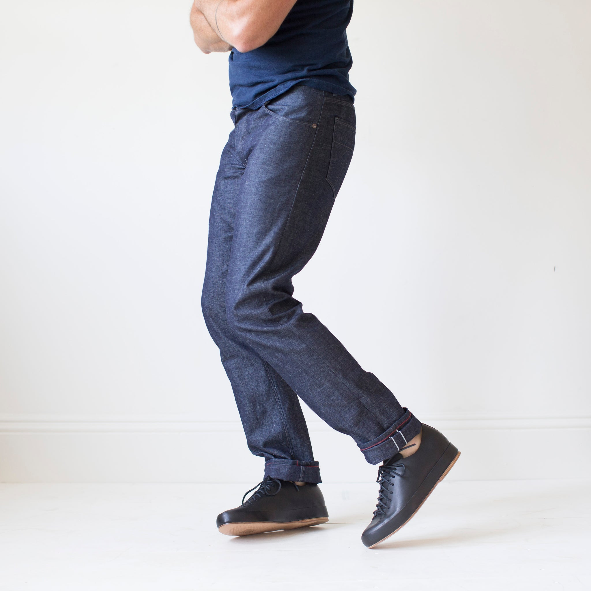 angle: wolf grey  A model wears Raleigh Denim Workshop men's Jones thin fit selvage raw denim jeans in grey, side view