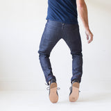 angle: wolf grey  A model wears Raleigh Denim Workshop men's Jones thin fit selvage raw denim jeans in grey, back view