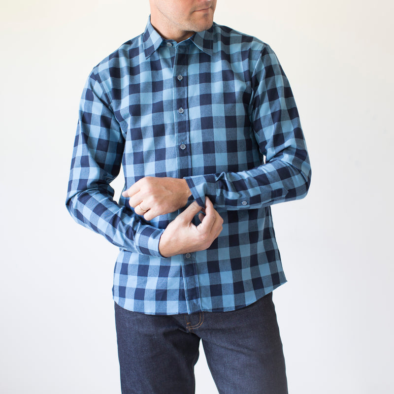 angle: large blue check  A model wears Raleigh Denim Workshop Classic Button-up men's shirt in blue and black checkered print, front view